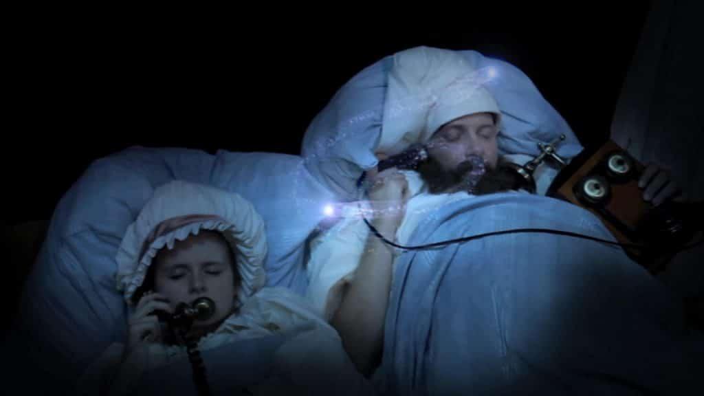 Kind und Mann mit Bart liegen im Bett